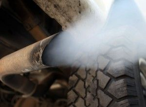 """MIAMI - JULY 11:  Exhaust flows out of the tailpipe of a vehicle at , """"Mufflers 4 Less"""", July 11, 2007 in Miami, Florida. Florida Governor Charlie Crist plans on adopting California's tough car-pollution standards for reducing greenhouse gases under executive orders he plans to sign Friday in Miami.  (Photo by Joe Raedle/Getty Images)"""