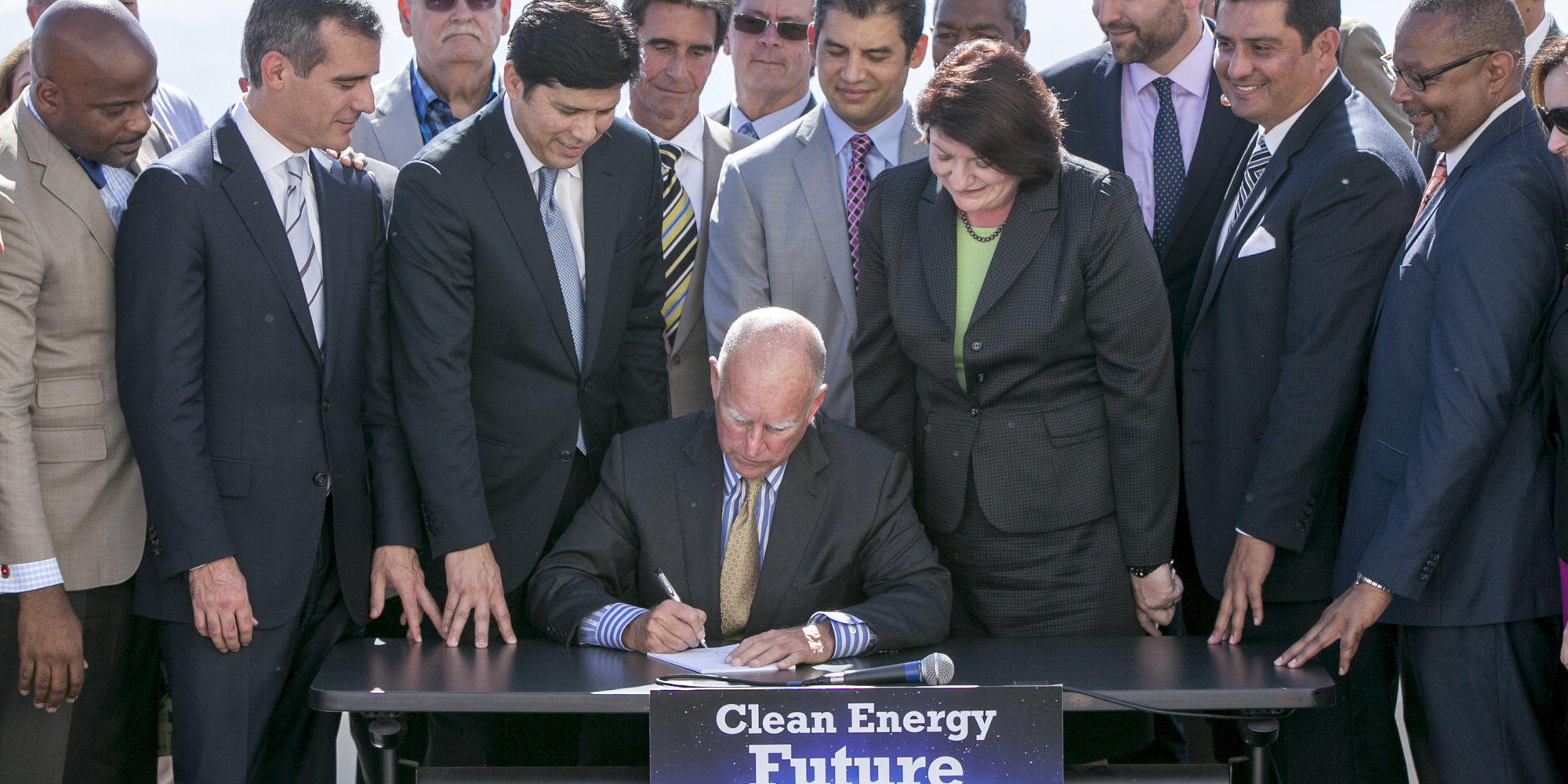 California Gov. Jerry Brown, sitting center, surrounded by government officials, signs landmark legislation, bill SB350 by Senate President pro Tempore Kevin De Leon, third from left, to combat climate change by increasing the state's renewable electricity use to 50 percent and doubling energy efficiency in existing buildings by 2030 at a ceremony at the Griffith Observatory in Los Angeles on Wednesday, Oct. 7, 2015. (AP Photo/Damian Dovarganes)